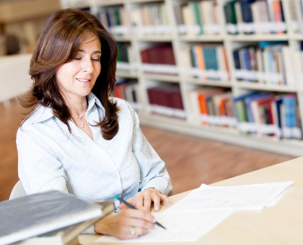 Female teacher grading exams at the library