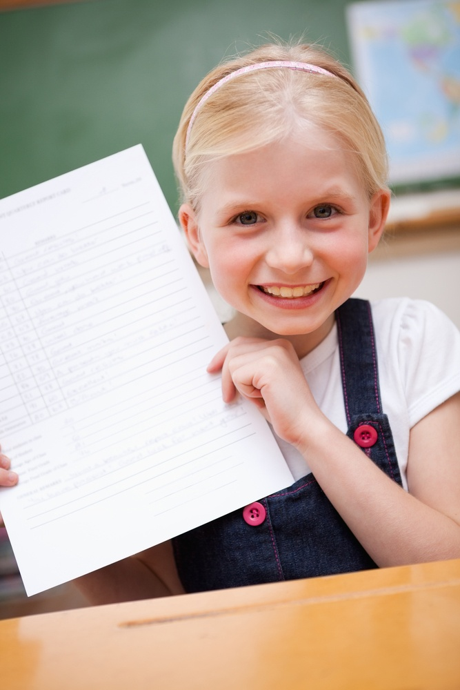 Portrait of a happy girl showing her school report in a classroom